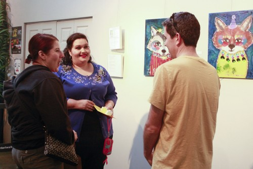 """Artist Elisa Rosas-Hutchison discusses her exhibit, """"Le Festival des Animaux (The Festival of Animals),"""" with friends Rod Leveque and Maryann Tolano-Leveque at the Claremont Art Walk Saturday. Rosas-Hutchison is a mixed media artist whose inspiration comes from childhood storybooks, fantasy and the idea of animals expressing human instincts. The Colony at Loft 204 in the Claremont Packing House is one of many galleries that host exhibits for the art walk on the first Saturday of every month./photo by Meghan Attaway"""