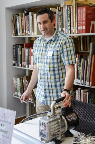 Physics lab manager BJ Haddad demonstrates his ping pong ball vacuum cannon at the Mini Maker Fair Monday in the Wilson Library. His vacuum repurposes atmospheric pressure to force the ping pong ball through a tube at around 300 mph. / photo by Emily Bieker