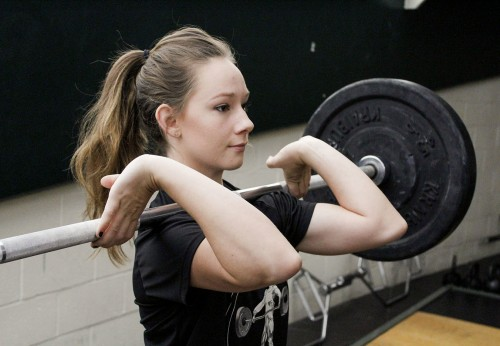 Junior Hailey McCann typically performs the snatch and the clean and jerk as she warms up for the rest of her workout. She begins with five kilograms and works her way up to her maximum of 67 kilograms./ photo by Brooke Grasso