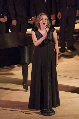 "Soprano Annie Johnson, junior music major, breaks from the choir to sing ""Fever"" by John Davenport and Eddie Cooley. The choir performed at ""The Birds and the Bees"" concert Saturday in Morgan Auditorium. The concert featured a collection of songs with themes of birds, bees and flight in the first part, and love in the second part. / photo by Terrence Lewis"