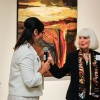 "Myra Garcia, a member of the President's executive committee, passes the microphone to artist Joella Jean Mohoney, who spoke about her art process Oct. 13 in the Harris Art Gallery. The opening reception focused on Mahoney's portfolio ""Passionate Vision: Landscape Painting of the Colorado Plateau 1965-2016 A Fifty Year Retrospective."" Mahoney has an master's degree in painting from Claremont Graduate School and is Professor of Art Emerita at the University of La Verne. / photo by Annette Paulson"