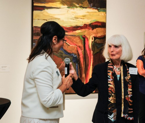 """Myra Garcia, a member of the President's executive committee, passes the microphone to artist Joella Jean Mohoney, who spoke about her art process Oct. 13 in the Harris Art Gallery. The opening reception focused on Mahoney's portfolio """"Passionate Vision: Landscape Painting of the Colorado Plateau 1965-2016 A Fifty Year Retrospective."""" Mahoney has an master's degree in painting from Claremont Graduate School and is Professor of Art Emerita at the University of La Verne. / photo by Annette Paulson"""
