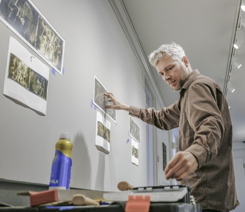 "Photography Department Manager Kevin Bowman arranges prints for ""Emblem and Artifice: Withered Symbols of the War,"" photography by J. Jason Lazarus, in the Carlson Galley. The exhibit features symbols of World War II on expired Kodabromide photographic paper from 1945. A reception with the photographer will be at 5 p.m. Nov. 10 in the Carlson Gallery. The exhibit runs through Dec. 16. / photo by Megan Peralez"