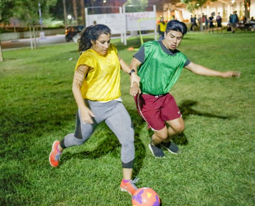 Junior business administration major Tina Kandah of the Phinest and freshman business administration major Adolfo Perez of Jesus and the Prophets battle for possession of the ball at the Latino Student Forum soccer tournament Wednesday. The Phinest won the match, 3-0. The team eventually won the tournament after beating the Phi Delts, 1-0. / photo by Michael Savall