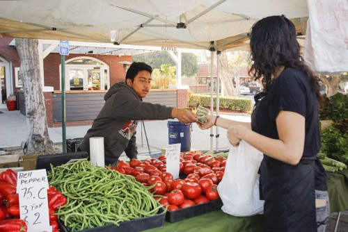 Bryan Valparaiso helps his father sell tomatoes, green beans and other fresh produce for Riverside-based RS Farms, at the La Verne Farmer's Market Saturday. Valparaiso said after the day is over, they return to Riverside and start loading produce for Sunday's farmers market in Claremont. Delia Heredia, who owns Delia's Barber and Beauty Shop on Third Street, was one of Valparaiso's first customers of the day. The farmers market is held every Saturday in on D Street in downtown La Verne. / photo by Berenice Gonzalez