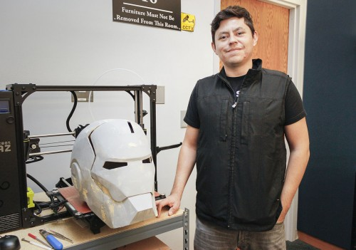 Alvaro Alvarez, technology support and applications specialist at the Wilson Library, has been working on a new 3-D project, an Iron Man mask. It took two weeks to print out all the parts. Alvarez said once he finishes painting the mask, it will be displayed in the front of the library. / photo by Berenice Gonzalez