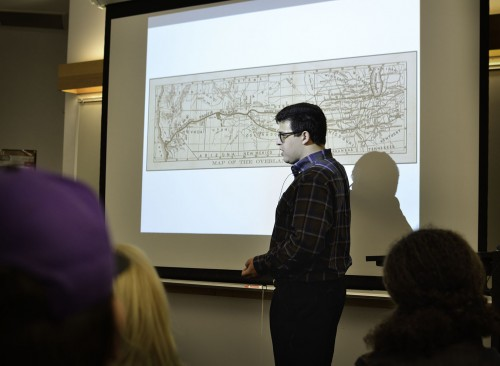 """Ben Jenkins, assistant professor and archivist, presents a summarized version of his dissertation Nov. 22 in the Wilson Library. In his lecture """"The Octopus's Garden,"""" Jenkins describes the octopus as an """"idealized version of the railroad grasping a bunch of different sections of California"""" such as farmers, miners and transportation routes across the United States. Jenkins spoke about the history of California starting as early as 1769, the economic impact of citrus growth and railroads and how capitalists modified the landscape for the railways. The lecture was sponsored by the La Verne Academy. / photo by Meghan Attaway"""
