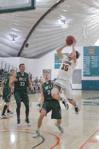 Junior guard Connor Head jumps ahead of Warriors' senior guard Tanner Schieve and sophomore forward Collin Kennedy in the first half of Sunday's non-conference game against Wisconsin Lutheran at Frantz Athletic Court. The Leopards defeated the Warriors, 84-72. / photo by Kathleen Arellano