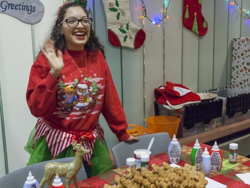 Associated Students of the University of La Verne President Alexis Coria, senior business administration major, invites students to decorate gingerbread men at a Christmas-themed table for the holidays. Students celebrated the winter holidays at the Campus Activities Board's Holiday Extravaganza Dec. 1 in the Campus Center. / photo by Donna Martinez