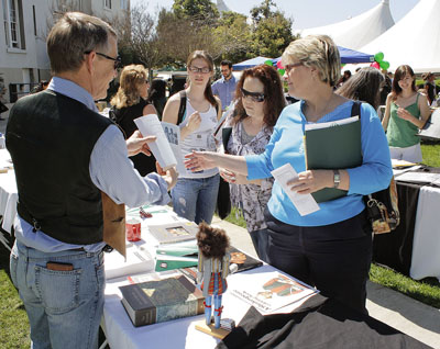 """Prospective students and their parents are invited to attend Spotlight @ ULV once each year. The event showcases opportunities at La Verne, including clubs and organizations, and academic departments. David Werner, professor of English, shows parent Terril Helander his chapter in the book, """"In The Shadow of the Hunter: What It Means To Be A Man."""" / photo by Rafael Anguiano"""