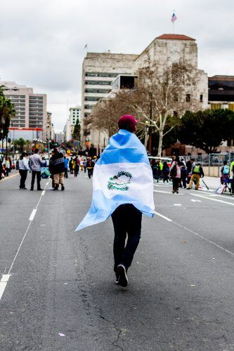 "During the Free The People Immigration March at the Los Angeles City Hall, a demonstrator from Argentina wraps his home country's flag around himself. ""I have never felt so attacked in all my years in this country,"" said Santiago Garcia, ""This is why I march today."" This photo was taken moments before aggressors with megaphones began to disrupt the peaceful protest. / photo by Benjamin Camacho"