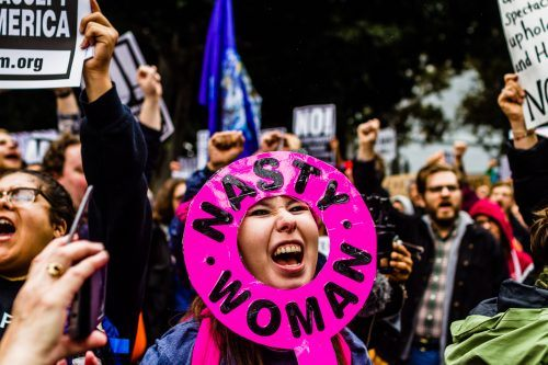 "Sporting a ""pussyhat"" in support of the Pussyhat Project, Laurel Trotter makes her voice heard through her ""Nasty Woman"" female symbol. Trotter was a demonstrator at the Not My Presidents Day rally on Feb. 20 at Los Angeles City Hall. / photo by Benjamin Camacho"