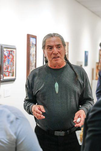 "Rogelio Briones, curator of the ""Fatal Beauty"" exhibit, talks to gallery visitors about the work on display during the reception at the College of Law Tuesday. The exhibit features work from 23 different artists, and will run until May 15."