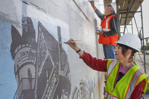 """Artists Joy McAllister and Chris Toovey work to restore """"Scrapbook,"""" the mural on the south side of the Arts and Communications Building on D Street facing Arrow Highway. The mural, based on historic photographs of old downtown La Verne, was first completed in 1992 as part of the city of La Verne's public art project. / photo by Tyler Deacy"""