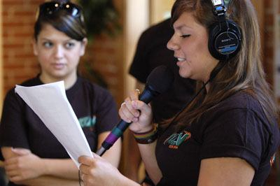 "Juniors Brittany Alarcon and Kristine Acosta broadcast from Davenport Dining Hall to mark KULV's change of format Sept. 17. As KULV, ""The Rock You Listen To,"" became Leo FM, ""Paw-pular Music,"" staff members of the station handed out free KULV t-shirts and rally towels, as well as cups featuring the new Leo FM logo. / photo by Leah Heagy"