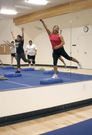 After an early lunch, many students gather in the athletics center for a session of step aerobics with Pam Maunakea, athletics departmental business manager. The class lasts for 50 minutes and students receive one unit for participating. At the Sept. 30 session, students Cassandra Juarez, Elizabeth Morales and Pricilla Ogas do their best to keep up with Maunakea and the fast-paced exercise music. Maunakea has been teaching the class at La Verne since 1991. / photo by Steven Bier