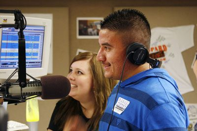 Senior radio broadcasting major Amy Smith assists Manuel Torres, a student from Norte Vista High School, as he learns to work the microphone on LeoFM during a live radio broadcast. Students from 25 high schools and three community colleges took part in workshops conducted by communications department faculty members Oct. 17 for the department's annual Communications Day. Leila Feinstein, KTLA news anchor, served as the event's keynote speaker. / photo by Steven Bier