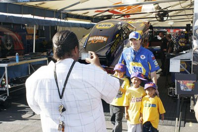 The National Hot Rod Association POWERade Drag Racing Finals were held last weekend at the Auto Club Raceway in Pomona. Ron Capps, with seven career No. 1 qualifiers, and driver of the first Funny Car sponsored by NAPA Autoparts, meets with fans of the NHRA POWERade Day racing series. The event was not just about racing but was about the fans as well. / photo by Rafael Anguiano