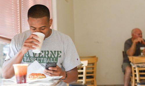 Junior business administration major Anthony White enjoys coffee and a croissant sandwich at Miss Donuts and Bagel before his Wednesday morning class. Many La Verne freshmen stay up until 4 a.m. – when Miss Donuts opens – to enjoy donuts fresh out of the fryer. Miss Donuts and Bagel, a La Verne institution, is at the corner of D Street and Bonita Avenue. /photo by Conor Holahan