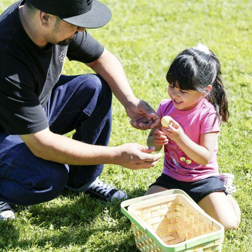 Rene Burguan helps daughter Abby open her eggs from the community Easter egg hunt Saturday at Las Flores Park. The event was co-sponsored by the La Verne Rotary Club and La Verne Community Services. / photo by Cierra Boess