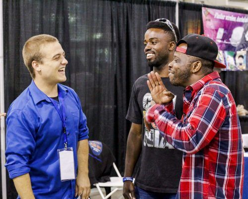 American Sign Language translator Dallas Stewart and expo visitors Larry Park and Jason Green share jokes in sign language at DeafUnited Expo, a touring trade show for the deaf community, Saturday at the Fairplex. / photo by Tyler Deacy