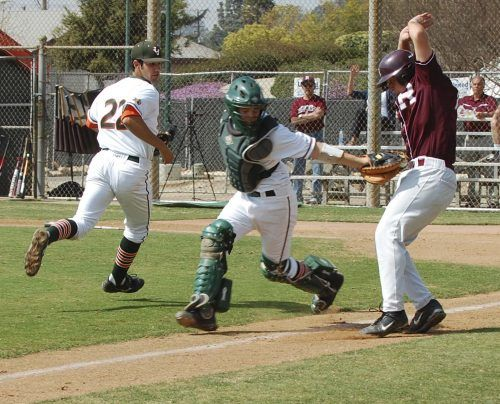 In a pickle between third baseman Aaron Coopman and catcher Mike Moretti, Redlands Bulldog Jefre Johnson is tagged out at home plate in the first inning. La Verne went on to lose to Redlands in the first game, 5-4, but came back to trounce the Bulldogs in the second game, 16-5. The Leopards will host the California Invite over the break. / photo by Jaclyn Dino