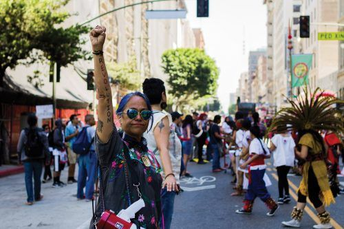 "Maria Sheldon, a demonstrator from the May Day General Strike, begins her march with a megaphone, giving directions and chants for the crowd behind her. A tattoo on her arm reads ""REVOLUTION."" This was the forefront of the march through downtown Los Angeles."