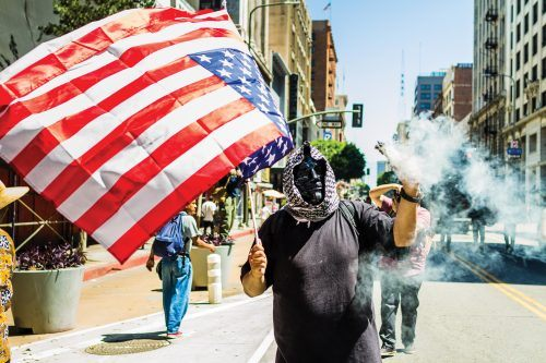 "An Antifa member marches with the liberal group during the General Strike. He burns sage and holds the American flag upside down in effort to show opposition for what Antifa considers a ""fascist regime."" This idea is prominently communicated by anti-fascist groups at most rallies. The burning of sage is a tradition originating from Native American cultures, it is believed that burning sage, or ""smudging"", blesses or protects a person."