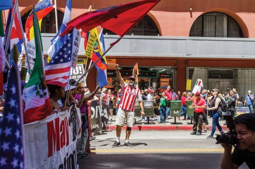 The start of the May Day General Strike began with immense energy from the people. Herardo Gomez raises his fist in effort to further rally up the marchers. An indigenous people's flag waves forward with the deep red color.
