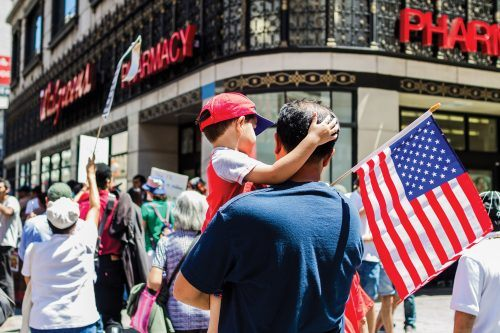 A man carries his son through the entirety of the march through the streets of Los Angeles. His son holds a water bottle for the both of them.