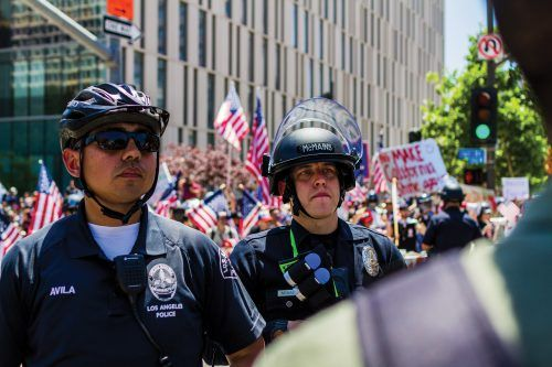 Los Angeles police officers Avila and McMains peer into the crowd, observing for any splurges of energy by potential aggressors. Trash and potentially harmful objects such as full water bottles or paint-filled condoms were thrown over the police line into the other crowd. Trump supporters would throw objects back or deflect them with shields brought from home.