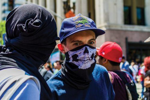 "Two Antifa members speak to each other about what the plan for the rest of the ""standoff"" is. The ""standoff"" was an all-day confrontation with Trump supporters, who arrived at 9 a.m. Antifa members met them at this time, and LAPD officers quickly rushed to prevent any fights or injuries. By the time the General Strike marchers arrived, Antifa members had blended into the crowd and maintained a low profile."
