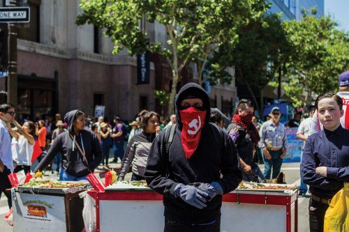 "A member of Antifa secures his gloves in preparation for what the Antifa group expected: a rumble. Antifa members wished to remain anonymous and refused to give out any names. This man arrived with several other members of Antifa; one of them carried a flag, most of them had backpacks that appeared to be full, others carried blunt objects. This man shows his beliefs on his face with a hammer and sickle bandanna, the symbol for communism. Behind him was a street vendor selling the well-known ""LA dogs"" which are hot dogs wrapped in bacon and grilled onions."