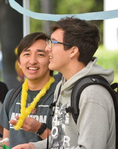 Freshman economics major Erick Flores and freshman chemistry major Ren Roth serve Hawaiian food to students at the Hawaiian Club's 'Get Lei'd' event. La Verne students enjoyed Hawaiian music, food, and hula dancing at the event Monday in the University Mall. / photo by Conor Holahan