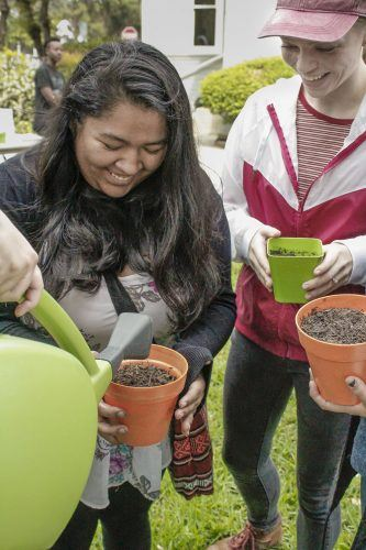 Freshman criminology major Maria Vargas and senior speech communications major Mikayla Thornley receive seeds to plant their own flowers during a showcase for the community garden behind the health center Tuesday, hosted by the Gardening Club. / photo by Tyler Deacy
