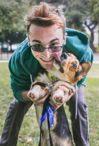 Junior computer science major Sean Gribbin plays with his year and a half old corgi Bruce in Sneaky Park. Gribbin said he hoped a a puppy would help fight his depression. He met Bruce through a corgi breeder in San Diego and said he bonded quickly with the runt of the litter. / photo by Cierra Boess