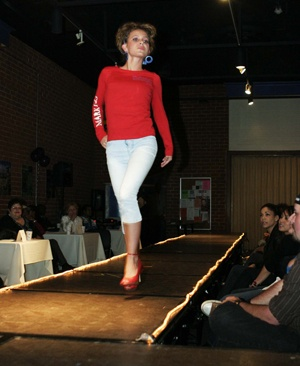 """Sara Weythman, a senior, models a red long-sleeved top at the Sister Circle fashion show Feb. 27. The top, which carries a Bible verse, is from Deeply Rooted Apparel, a clothing company with """"fashion that brings together a lasting style for the progressive Christian."""" / photo by Rhiannon Mim"""