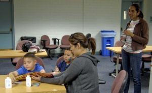 Maria Leib read a book about the life cycle of the butterfly to her two boys, Michael and Tyler Leib, under the watchful eye of junior Alicia Lopez. Lopez volunteered at the Family Literacy Fair in the Hoover Building on Saturday. / photo by Sher Porter