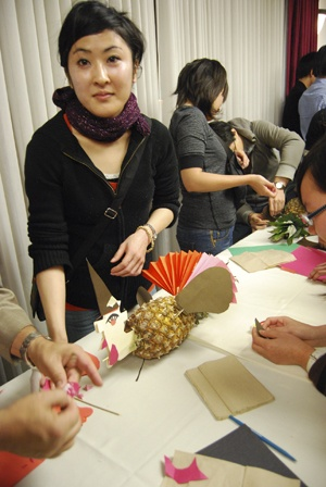 The International and Study Abroad Center, together with the College of Business and Public Administration, hosted a Thanksgiving dinner for international students on Nov. 17. During the dinner, students experienced Thanksgiving as a traditional festival in the United States. Philip Hofer, director of the International and Study Abroad Center, taught students to make a pineapple turkey decoration for each table. Chieko Abe, from Japan, is studying for a master's of science degree in child life. / photo by Wei Huang