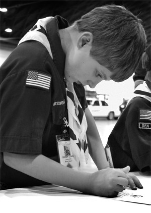 """Members of Upland Boy Scout Pack 614 enjoyed the events of the  police expo, held Saturday at the Fairplex. More than 50 police departments participated in the event, which included K-9 demos, displays of guns and cars. Boy Scout Derek Long participated by writing a card for a United States soldier in Iraq at the """"Soldiers' Angels'"""" booth. Soldiers' Angels' mission is to provide aid and comfort to those serving in the military. / photo by Rhiannon Mim"""
