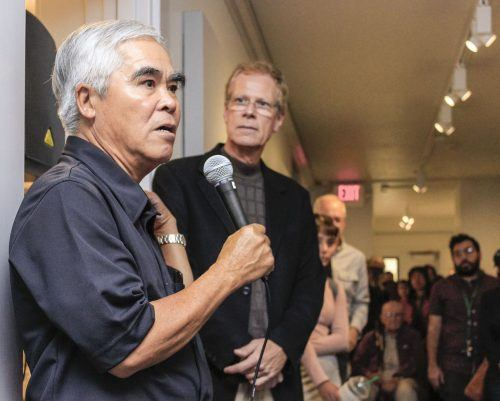"""Students and faculty fill the Carlson Gallery to hear Vietnamese-American photographer Nick Ut speak at a reception Sept. 21. The Pulitzer Prize-winning photojournalist's historic and contemporary pictures are on display here until Oct. 13. Ut is best known for his Vietnam War photography, particularly """"Napalm Girl,"""" for which he won the Pulitzer. / photo by Spencer Croce"""