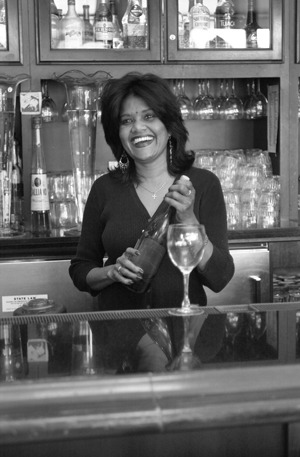 Walter's Restaurant is located at the corner of Bonita and Yale in the Claremont Village. It serves a variety of American, French, Afghan and Middle Eastern cuisines. Waitress Bina Sharkey, a five-year employee at Walter's, pours a glass of wine for a customer. / photo by Kelly Rivas