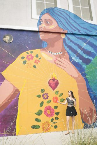 Anakarla Sigala, senior criminology major, mimics the woman in the Wilson Library mural. The artist, Kristy Sandoval, liked that Sigala had pieces of her hair dyed blue and wore a traditional Mexican blouse. The mural was completed as part of the University's 125th anniversary celebration. / photo by Celeste Drake