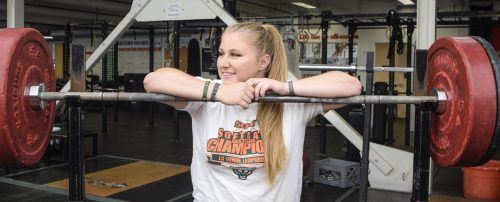 When senior kinesiology major and softball catcher Angelica DeAngelo started her freshman year, the softball team's squat lift record was 195 pounds. During her junior year DeAngelo broke the record twice, once in the beginning of the year squatting 200 pounds and again at the end of the year squatting 216 pounds. DeAngelo trained five days a week over the summer to break the record again. Last month, DeAngelo reset the record to 235 pounds. / photo by Audrey Gaudette