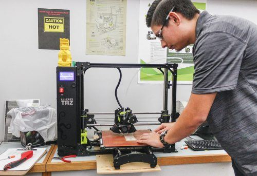 Freshman computer science major Alex Lara demonstrates how to use a 3D printer in the Makerspace of the Wilson Library Tuesday. The Lulzbot printer can make its own parts, making it almost completely self-sustaining. A product line of Aleph Objects Inc. the Lulzbot products are produced as open-licensed designs, enabling users to easily modify and replace parts. / photo by Celeste Drake