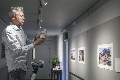 "Kevin Bowman, photography department manager, installed the latest photography exhibition, ""Life on Wheels: The New American Nomads"" by David Gardner, in the Carlson Gallery. In this series, Gardner captures moments of the lives of Americans who have decided to live on the road in recreational vehicles instead of living in a traditional home. A reception with Gardner will be held from 5:30 p.m. to 7 p.m. Wednesday in the gallery. / photo by Nadira Fatah"
