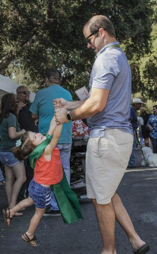 Alex Lester and his daughter, Arianna, dance at the 2017 Homecoming street fair and parade on Saturday. Lester graduated from the University of La Verne in 2008, and from the ULV College of Law in 2011. He works for an Upland law firm and has served on the University of La Verne Board of Trustees since 2014. The street fair featured Marvel Comics superhero-themed games and activities. This year the University honored Homecoming Heroes instead of Homecoming king and queen. / photo by Spencer Croce