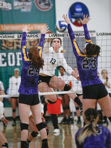 La Verne junior middle blocker Katelyn Winiecki spikes the ball between two Whittier players, senior middle blocker Alexis Mills and freshman outside-hitter Ashley Whittall, in the first set against the Poets Saturday. The Leopards won the match in four sets at Frantz Athletic Court. / photo by Brenna Ulsh