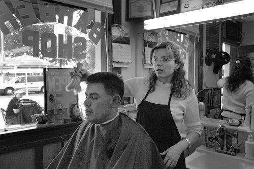 """Delia is nice; that's why I come here,"" customer Albert Preciado said about Delia Heredia, owner of Delia's Barber and Beauty on Third Street. Heredia, who started her business on May 3, 2000, said, ""Styling hair is one of my passions."" / photo by Reina Santa Cruz"