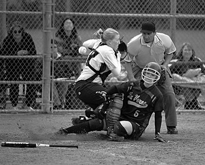 A base hit with the bases loaded allowed Amber Guerra (No.5) of the Leopards to come home safe against Oaks catcher Jessica Courson (No.17), Saturday at Wheeler Park. The University of La Verne's softball team prevailed with an 8-0, 9-0 doubleheader sweep over Menlo College. They take on the University of Redlands in a three game series this week. / photo by Jenna Campbell